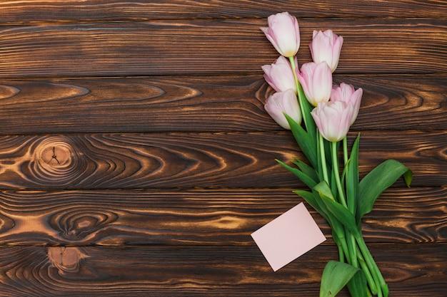 Tulipanes y tarjeta con etiqueta vacía en mesa oscura