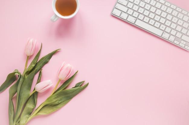 Tulipanes con taza de té y teclado