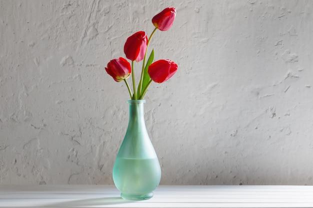 Tulops rojos en florero sobre mesa blanca