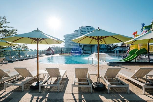 Tumbona y piscina en hotel.