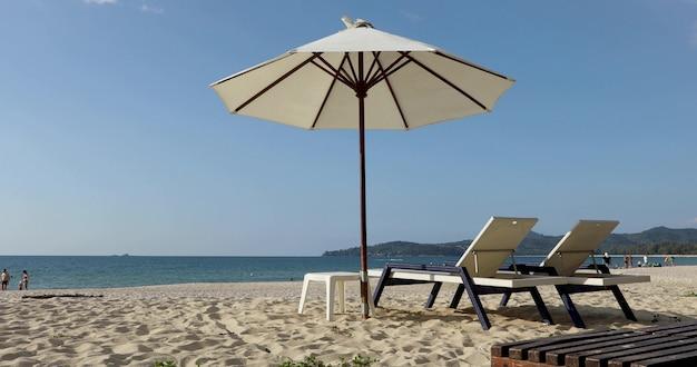 Tumbonas vacías en la playa exótica en tailandia con personas en el fondo