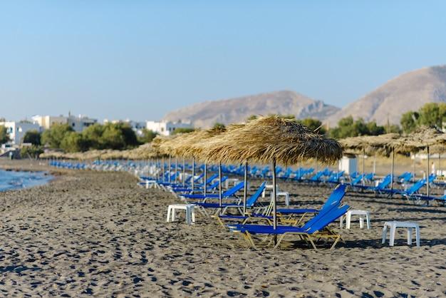 Tumbonas vacías en la playa de perissa. santorini