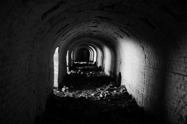 Túnel de ladrillo de miedo en la oscuridad y algo de luz.