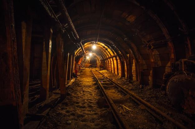 Túnel minero subterráneo con rieles.