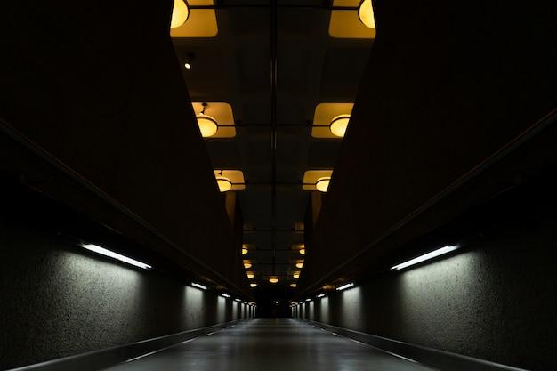 Túnel oscuro con lámparas encendidas en el techo.