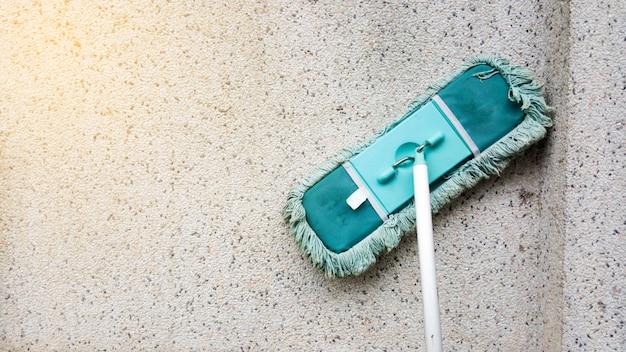 Una turba o un hisopo verde y sucio se apoyan en un muro de concreto sucio.