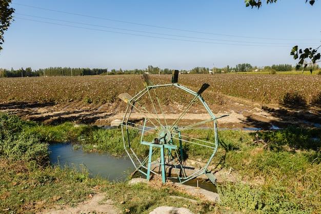 Turbina de agua en un campo de algodón. rueda de agua y canal para regar las plantas en el campo, uzbekistán