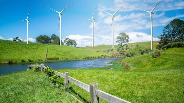 Las turbinas de viento cultivan en colinas de una hierba verde.