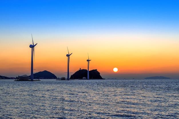 Turbinas de viento que generan electricidad al atardecer en corea