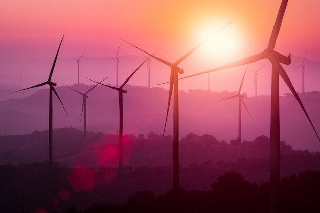 Turbinas de viento silueta en las montañas al atardecer.
