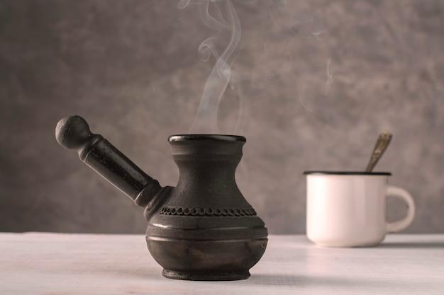 Turco de arcilla vintage usado para café con una taza blanca sobre un fondo gris