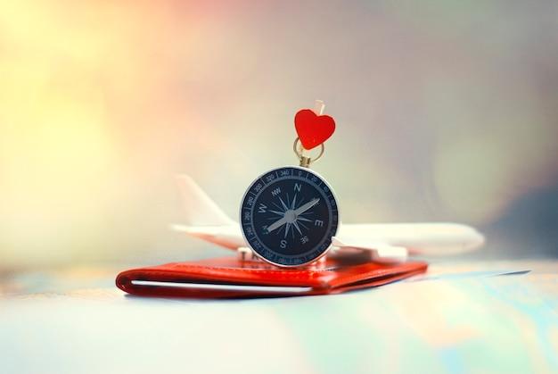 Turismo con avión, pasaporte y pasajes y brújula con corazón.