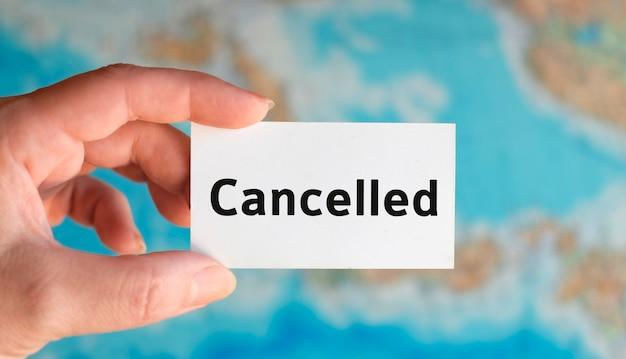 Turismo cancelado: texto en una hoja blanca en el fondo del mapa del atlas
