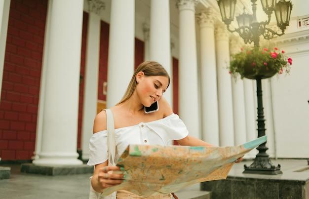 Turismo de mujer joven belleza explorar mapa de la ciudad y hablar por teléfono