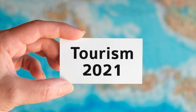 Turismo mundial 2021: texto en una hoja blanca en la mano sobre el fondo del mapa del atlas