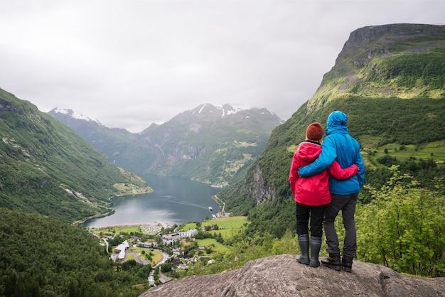 Turismo en noruega. una joven pareja disfrutando de una vista increíble de un fiordo y un valle montañoso. pueblo turístico de geiranger y geirangerfjord