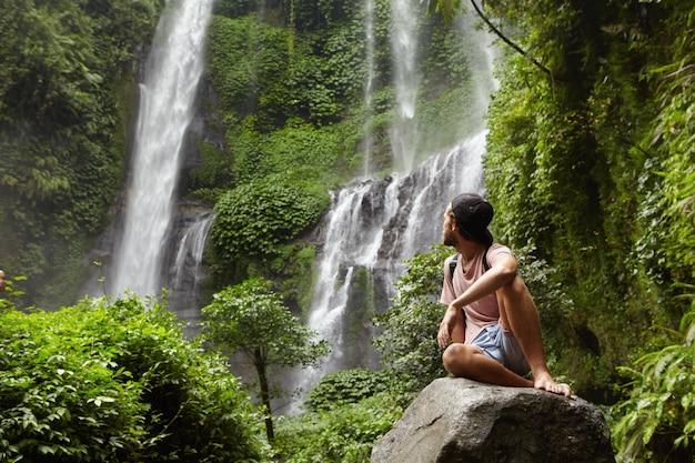 Turismo, viajes y aventura. elegante joven inconformista sentado en piedra con los pies descalzos y volviendo la cabeza hacia atrás para ver una cascada increíble
