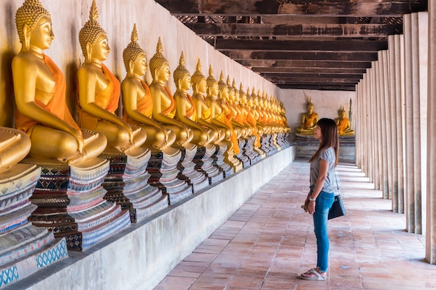 Turista adolescente tomar una foto antigua pagoda de wat phutthaisawan es budista