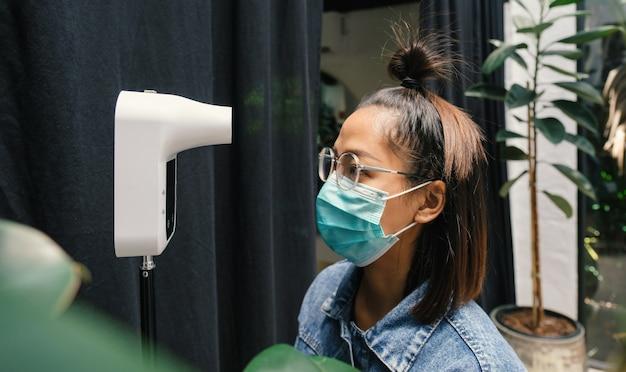 La turista asiática ha comprobado la temperatura corporal con un detector de escáner de temperatura térmica