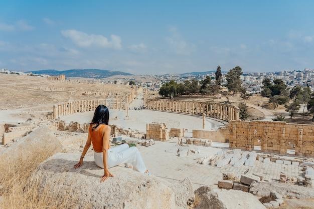 Turista asiática de la mujer joven en vestido y sombrero del color que disfruta del foro oval en la ciudad romana antigua