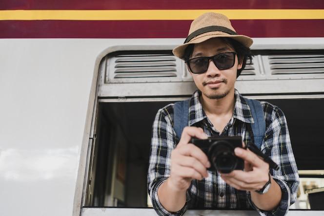 Turista asiático del paquete del bolso del hombre con la cámara en el ferrocarril en tailandia.