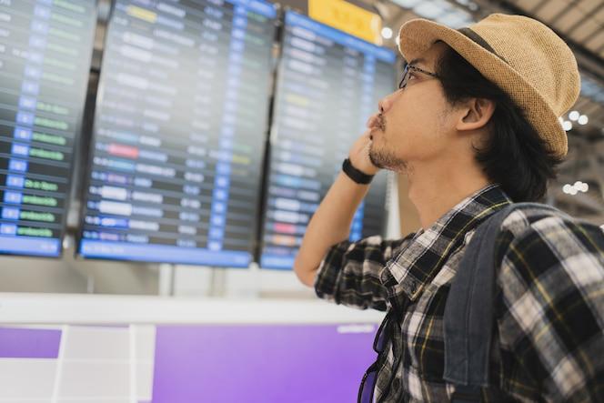 Turista asiático del paquete del bolso del hombre en aeropuerto.