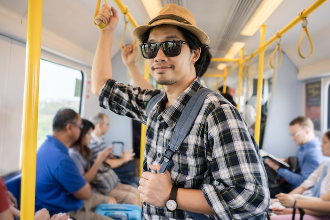 Turista asiático del paquete del bolso del hombre en un tren.