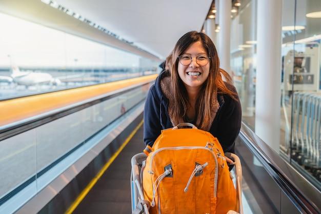 Turista asiático feliz y emocionado de viajar, caminando y sonriendo cuando camina a través de una escalera mecánica