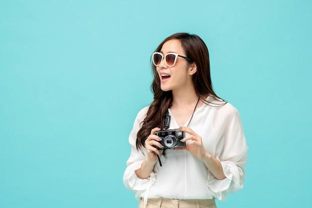 Turista asiático femenino joven que sostiene una cámara