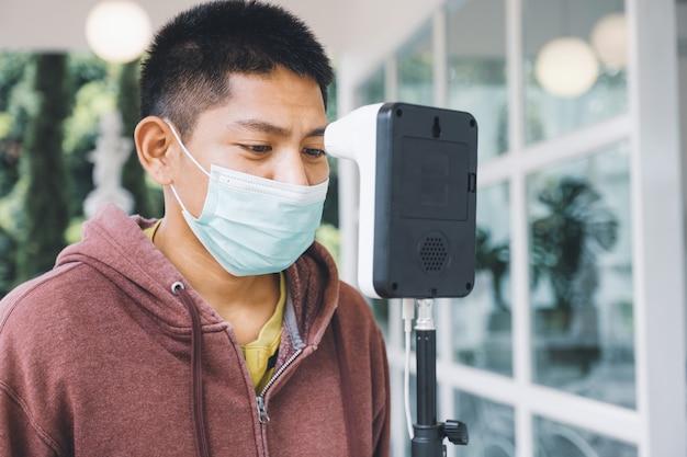 Un turista asiático ha comprobado la temperatura corporal con un detector de escáner de temperatura térmica nuevo normal