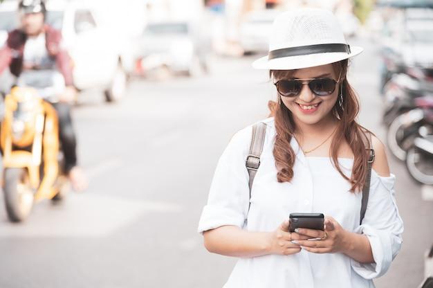 El turista asiático de la mujer está comprobando el teléfono inteligente que manda un sms en la calle, usando el teléfono móvil app para comprobar el mapa en línea.