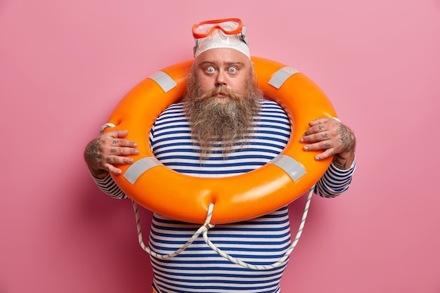 Turista asustado con sobrepeso que teme hundirse, usa equipo de seguridad, usa gafas para bucear, nada con aro salvavidas, mira directamente con expresión de asombro. seguro de viaje