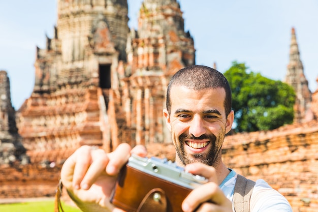 Turista en ayutthaya tomando un selfie con cámara vintage