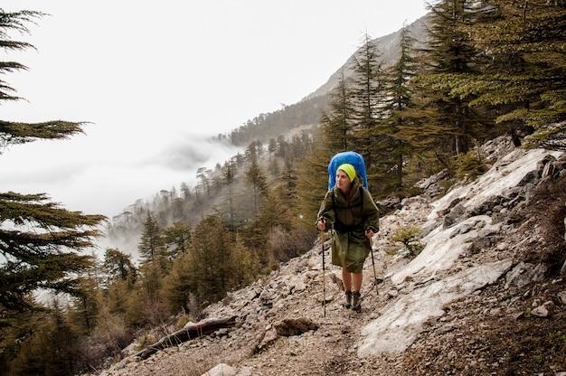 Turista baja la montaña en el bosque