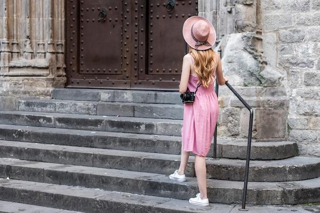 Turista bonita rubia caucásica con un sombrero tomando fotos de la ciudad