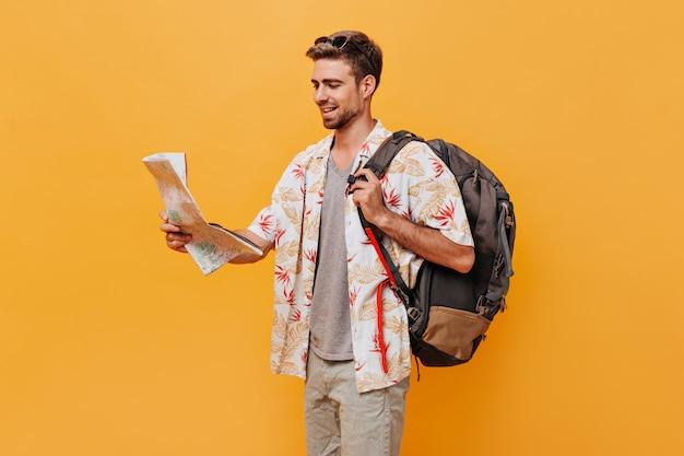 Turista bronceado en traje fresco de moda y gafas de sol posando con mochila y mapa en pared naranja aislada