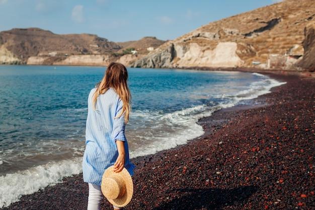 Turista caminando por la costa de la playa roja en akrotiri, isla de santorini, grecia. concepto de viaje y vacaciones
