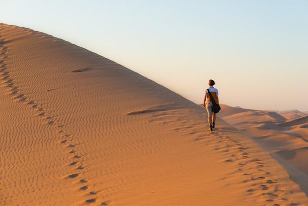 Turista caminando sobre dunas escénicas en el desierto de namib, namibia