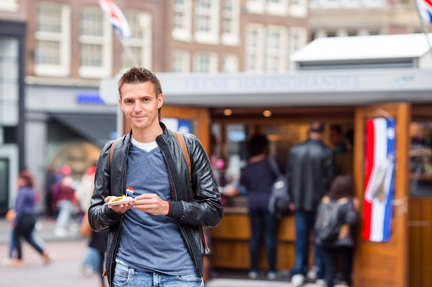 Turista caucásico feliz con arenque fresco con cebolla y bandera de holanda en amsterdam.