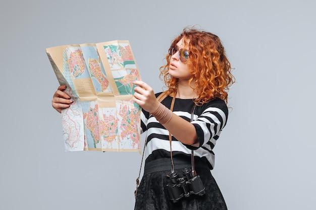 Turista chica pelirroja mirando un mapa