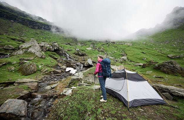 Turista en la cima de la colina en las montañas