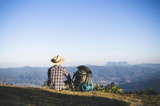 Turista desde la cima de la montaña. rayos de sol. hombre usa mochila grande contra la luz del sol