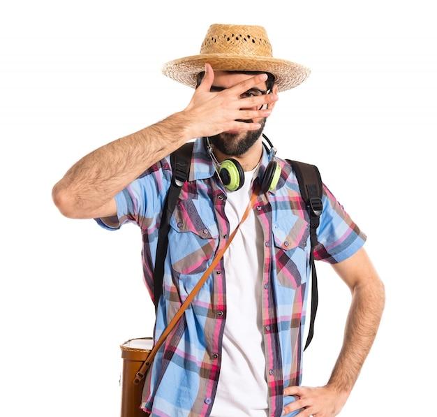 Turista cubriendo su cara