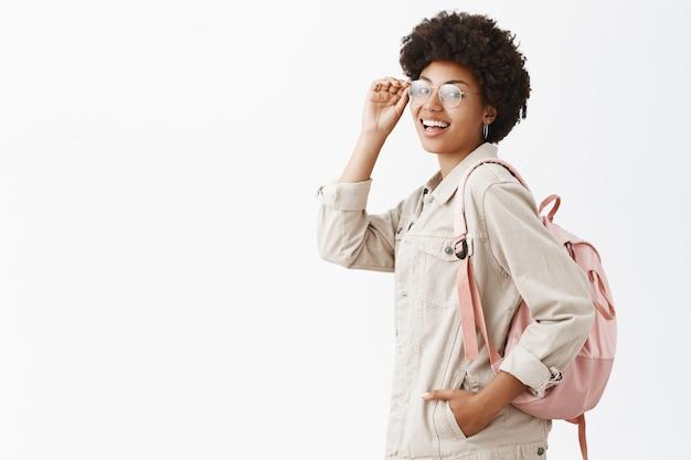 Turista elegante y guapa con piel oscura y peinado afro que revisa las gafas en los ojos y gira mientras está de perfil sobre una pared gris
