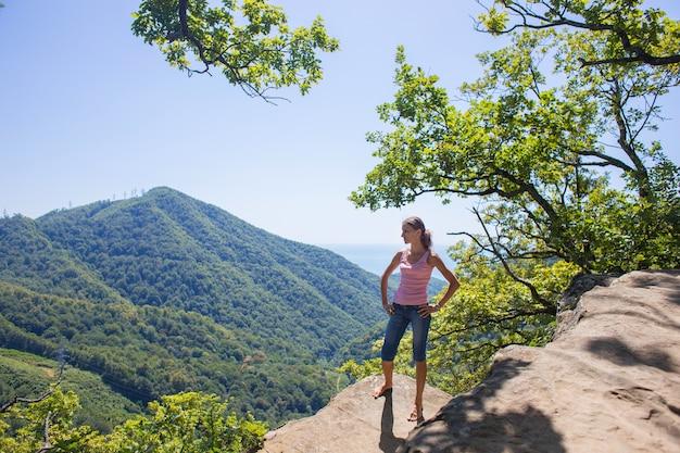 La turista se encuentra en un acantilado de una alta montaña con el telón de fondo de la hermosa naturaleza y el mar y mira hacia otro lado