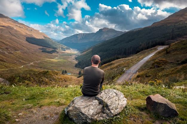 Turista en escocia se sienta de espaldas a la cámara