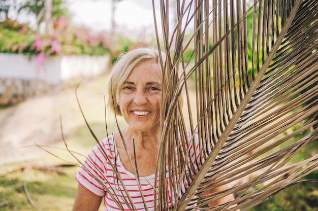 Turista europeo mayor que viaja turístico sonriente de la mujer que camina disfrutando en la selva tropical de sanya. viajando por asia, concepto de estilo de vida activo. descubriendo hainan, china. posando con rama de palma