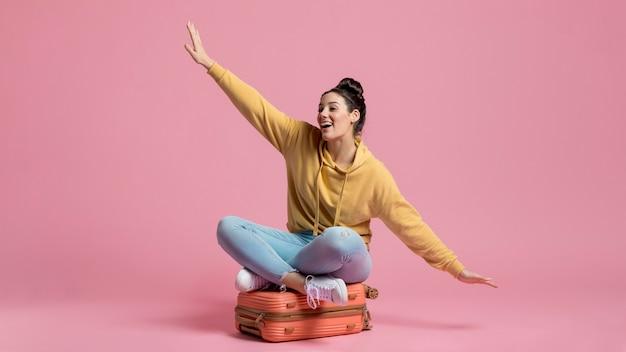 Turista feliz sentado en el equipaje