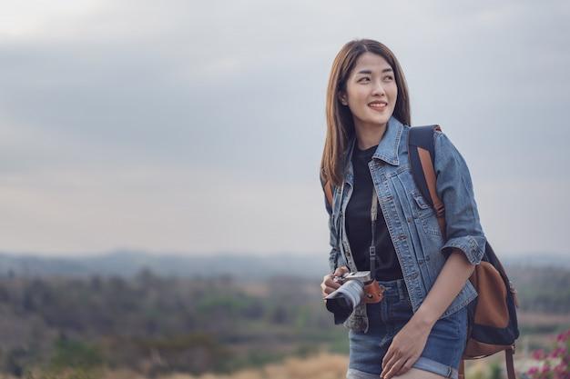 Turista femenina con mochila y cámara en campo