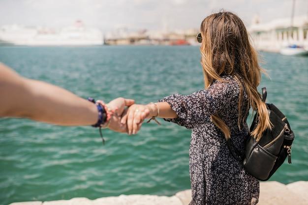 Turista femenina que mira el mar que lleva a cabo la mano de su novio